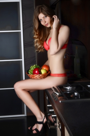 The woman in underwear with a basket of fruit on kitchen photo