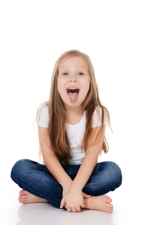 teasing: The little girl puts out the tongue isolated Stock Photo