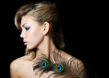The beautiful woman with feathers of peacock photo
