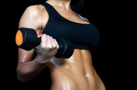 Beautiful brawny body of woman with dumbbells photo