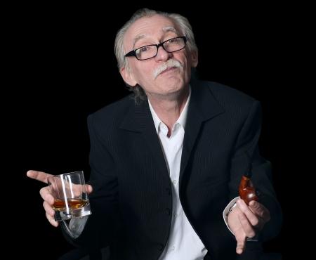 Der ältere Mann mit einem Glas Whisky auf einem schwarzen Hintergrund