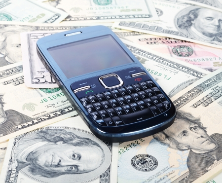 Cellular phone on dollars as a background photo