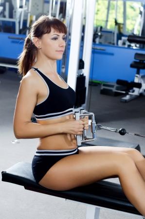 aide à la personne: Femme sur un appareil de formation de club de sport