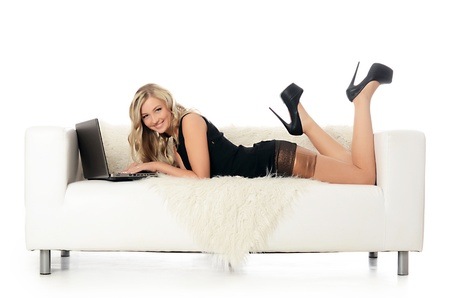 The elegant woman on a white sofa with the laptop. Business concept. Stock Photo - 20674688