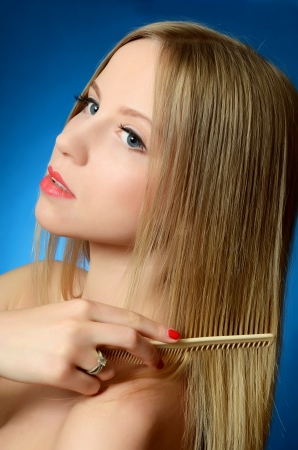 The beautiful girl brushes hair on blue photo