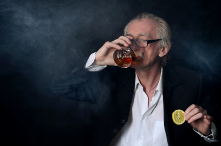 The elderly man with a glass of whisky on a black background photo