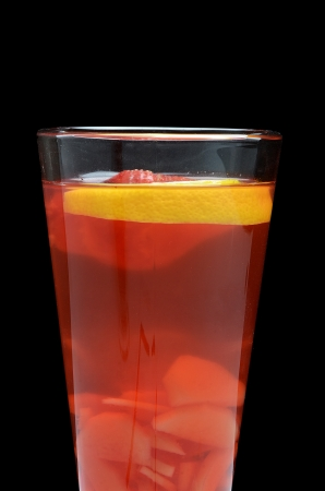 tall glass: Cold red fruit tea with an orange Stock Photo