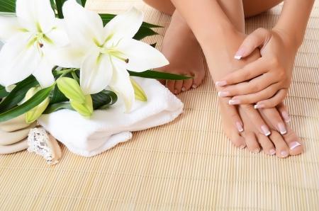Mano de la mujer, los pies con pedicura y manicura al lado de un par de lirios