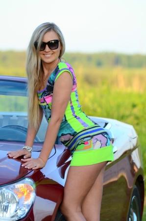 Schönes Mädchen steht in der Nähe von roten Auto