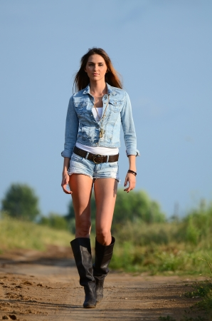 The woman in jeans shorts on road photo