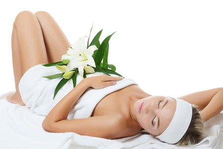 sensual massage: Spa beautiful woman lays with white lily