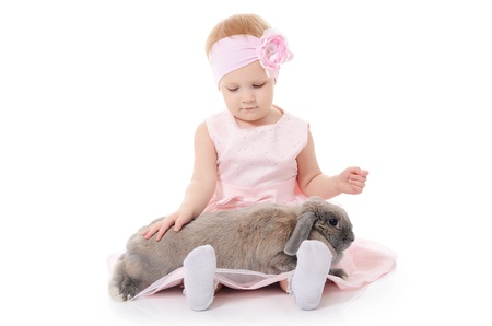 The little girl with a grey rabbit isolated on white photo