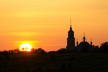 Silhouette of church against a sunset photo