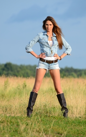 The woman in jeans shorts in field photo