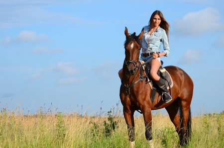 The woman on a horse in field photo