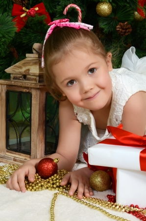 The little girl at a Christmas fur-tree with gifts photo