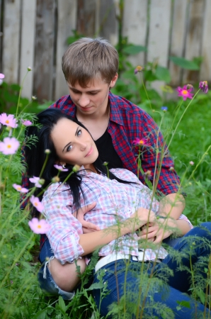 Enamoured young pair in field with flowers photo