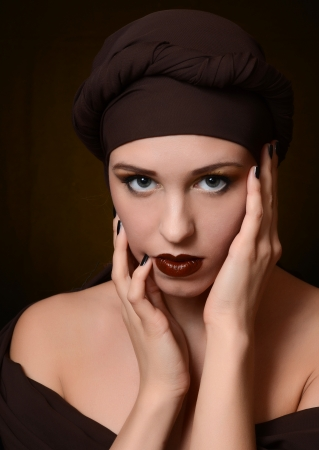 The beautiful woman in a turban with a creative make-up photo