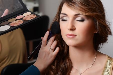 Hermosa chica poner el maquillaje en la cara