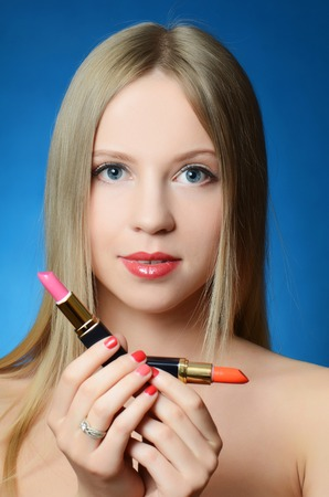 The beautiful woman with lipsticks in hands photo