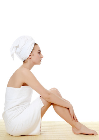 The beautiful woman in a towel on bamboo rug. SPA concept. photo