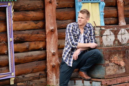 The beautiful man against a wooden house photo