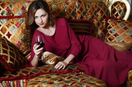 Sensual woman with a red wine glass on a magnificent sofa Stock Photo - 25934422