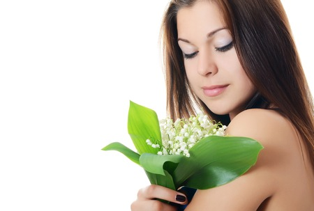 The beautiful woman holds a flower of a lily of the valley photo