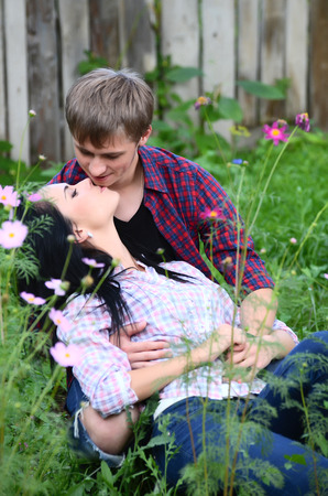 enamoured: Enamoured young pair in field with flowers Stock Photo