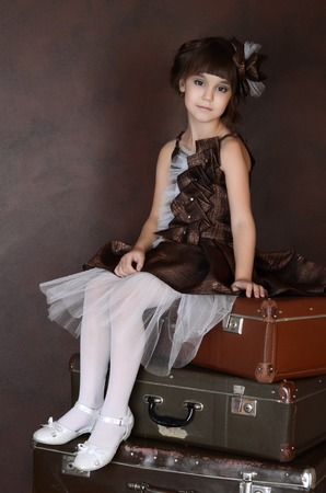 The little girl with old retro suitcases photo