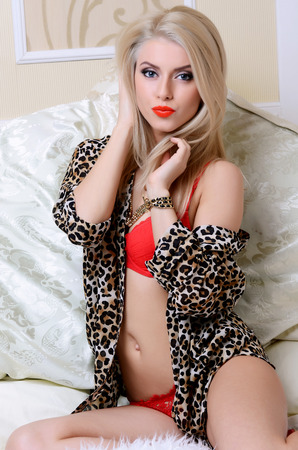 The beautiful blonde girl on a bed photo