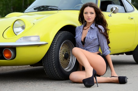The beautiful woman with yellow retro car photo