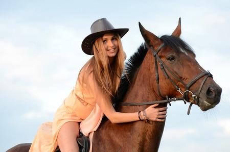 Die Frau auf dem Pferd gegen den Himmel Standard-Bild