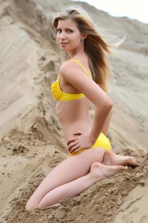 The beautiful woman in bikini on sand photo