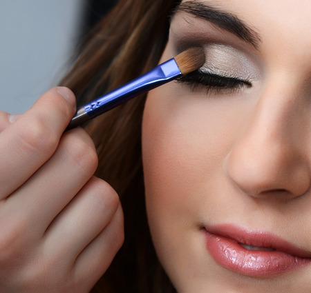 Beautiful girl put the makeup on the face photo