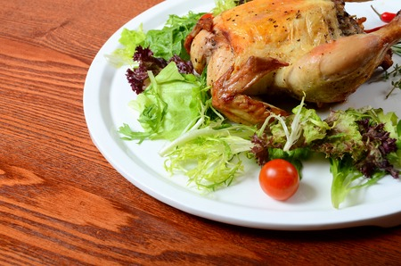 The baked hen with salad close up photo