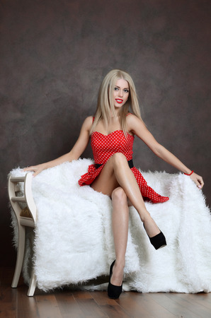 sits on a chair: Beautiful sensual woman sits on a chair