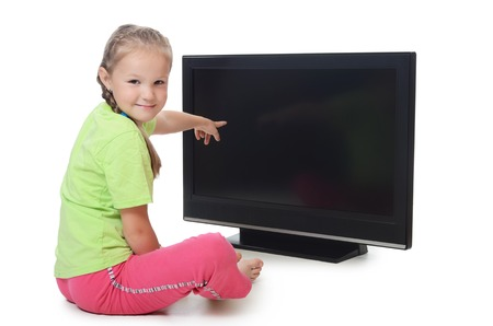 The little girl looks to an LCD TV isolated in white. photo