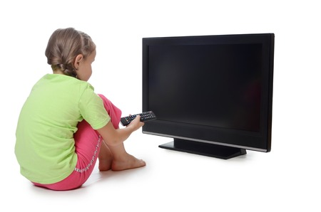 little girl sitting: The little girl looks to an LCD TV isolated in white.