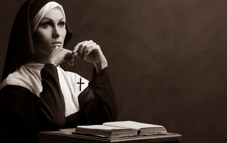 Young attractive nun praying photo