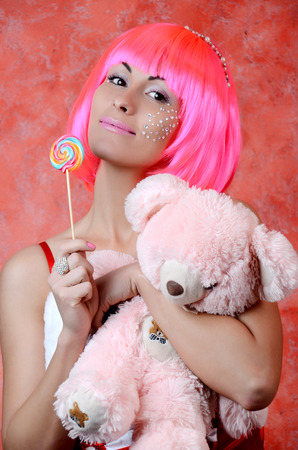 woman laughing with candy and beautiful make-up  whith taddy bear photo
