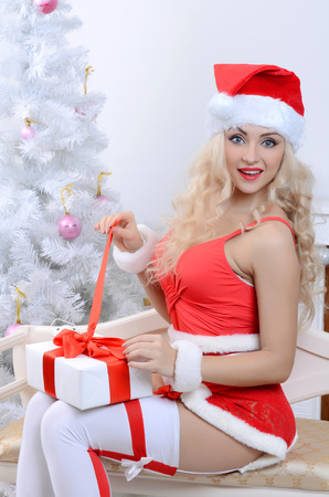 young beauty smiling santa woman near the Christmas tree photo