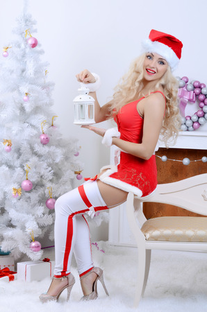 Young beauty smiling santa woman near the Christmas tree photo