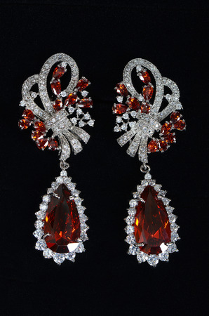 Silver earrings with jewels on the black photo