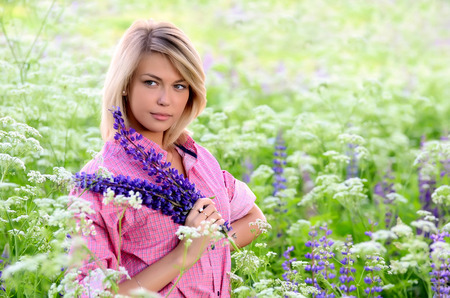 lupin: The beautiful woman in field with lupin Stock Photo