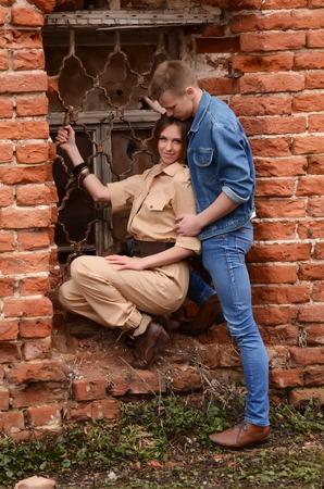 enamoured: Young enamoured pair at a brick wall Stock Photo