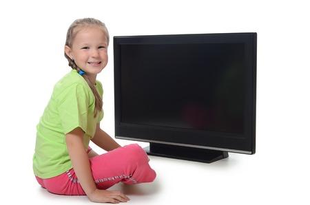 little girl sitting: The little girl looks lsd tv isolated