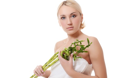 The beautiful young woman with a green bamboo isolated photo