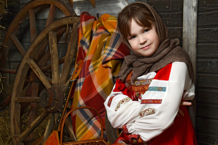 log basket: Beautiful girl in russian costume sitting in a traditional interior