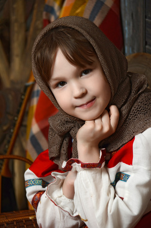 Beautiful girl in russian costume sitting in a traditional interior photo